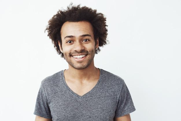 Porträt des glücklichen und charmanten afrikanischen kerls, der lächelt, ein freund, der auf ein datum wartet, oder ein kopfjägertraum, der über weißer wand steht.