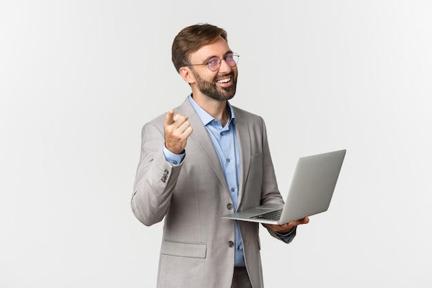 Porträt des glücklichen und erfreuten geschäftsmannes im grauen anzug und in der brille, die mit laptop arbeiten