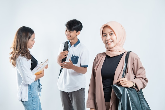 Porträt des glücklichen universitätsdozenten, der taschen und junge leute des campus trägt, die auf isoliertem weiß plaudern