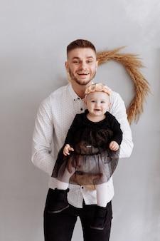 Porträt des glücklichen vaters und seiner entzückenden kleinen tochter auf seinen händen zu hause. glückliche kindheit. vater umarmt sein kleines mädchen mit liebe. familienlook.