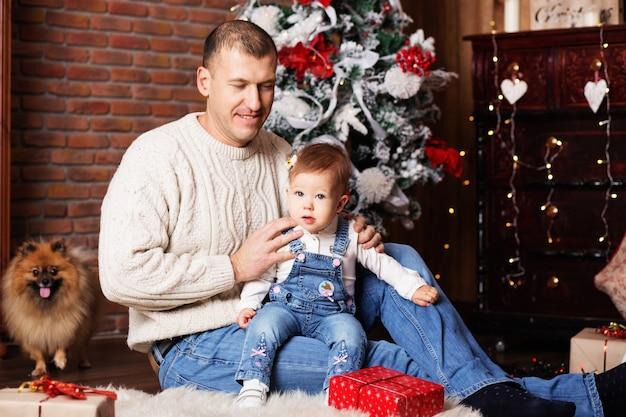 Porträt des glücklichen vaters und seiner entzückenden kleinen tochter unter weihnachtsdekorationen