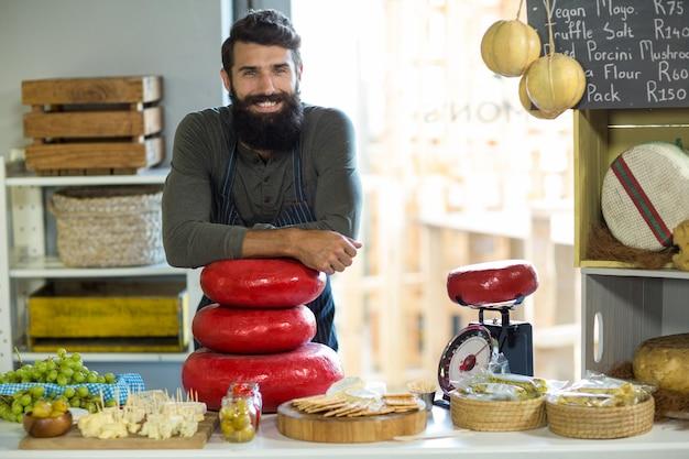Porträt des glücklichen verkäufers, der am schalter steht