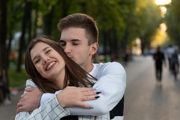 Porträt des glücklichen verliebten paares im park. guy umarmt seine geliebte an den schultern.