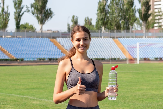 Porträt des glücklichen weiblichen athleten, der eine flasche wasser und daumen oben auf dem stadion hält.
