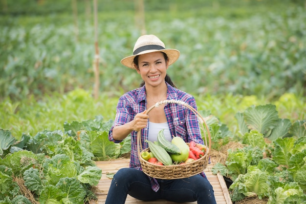 Porträt des glücklichen weiblichen landwirts, der einen korb des gemüses im bauernhof hält