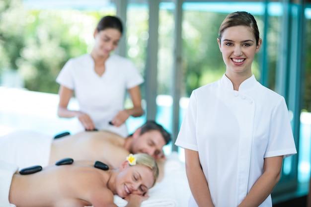 Porträt des glücklichen weiblichen masseurs im badekurort