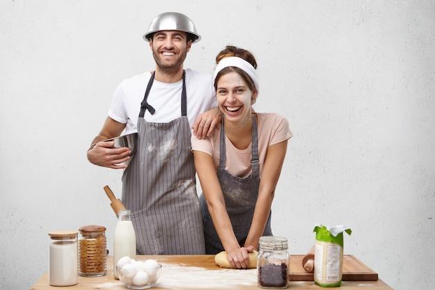 Porträt des glücklichen weiblichen modells knetet teig mit lächeln, steht nahe männlichem kollegen, arbeiten zusammen