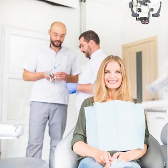 Porträt des glücklichen weiblichen patienten, der vor männlichem zahnarzt zwei sitzt