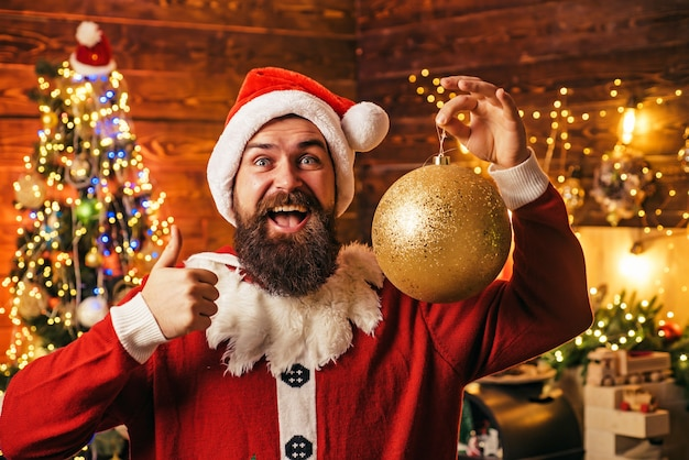 Porträt des glücklichen weihnachtsmanns mit dekorativen spielzeugkugeln nahe weihnachtsbaum