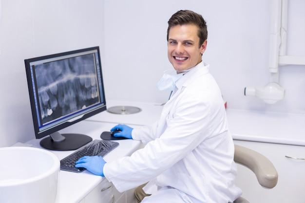 Porträt des glücklichen zahnarztes, der röntgenbericht auf computer untersucht