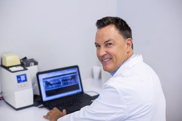 Porträt des glücklichen zahnarztes, der röntgenbericht auf laptop untersucht