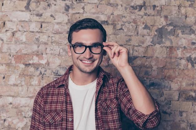 Porträt des glücklichen zahnigen klugen mannes, der seine brille berührt