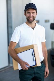 Porträt des glücklichen zustellers, der paket und zwischenablage hält