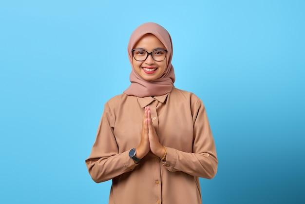 Porträt des glücks junge asiatische frau, die hand auf plädoyer über blauem hintergrund hält