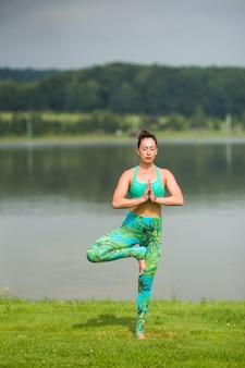 Porträt des glücks junge frau, die yoga im freien praktiziert