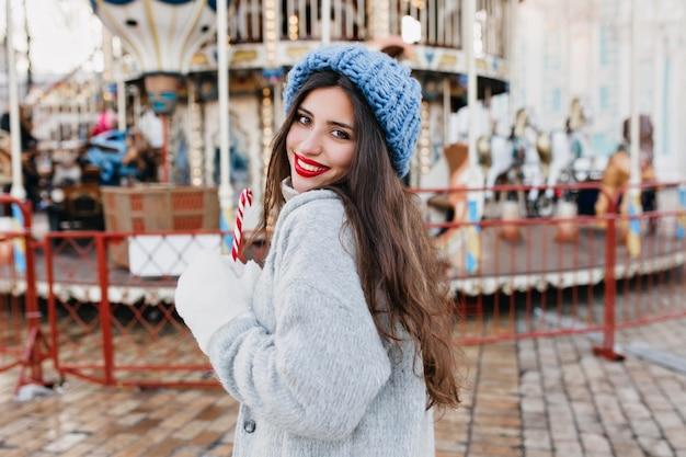 Porträt des glückseligen langhaarigen weiblichen modells in den weißen handschuhen, die zuckerstange im vergnügungspark halten. hübsches mädchen im blauen hut, das weihnachten feiert und nahe karussell aufwirft.