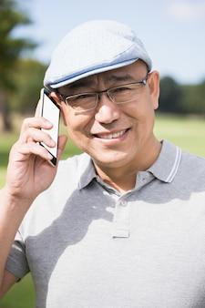 Porträt des golfers, der lächelt und anruft