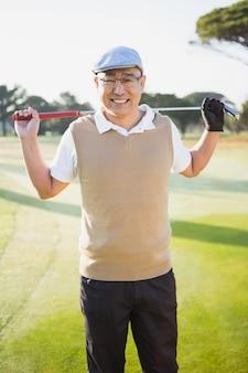 Porträt des golfers, der lächelt und seinen golfschläger hält