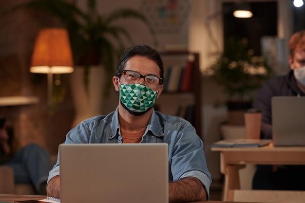Porträt des grafikdesigners in der schutzmaske, die vorne beim arbeiten am laptop am tisch im büro schaut
