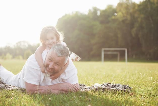 Porträt des großvaters mit der enkelin, die zusammen im park entspannt