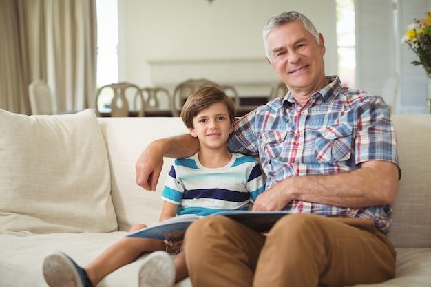 Porträt des großvaters mit ihrem enkel, der buch auf sofa hält