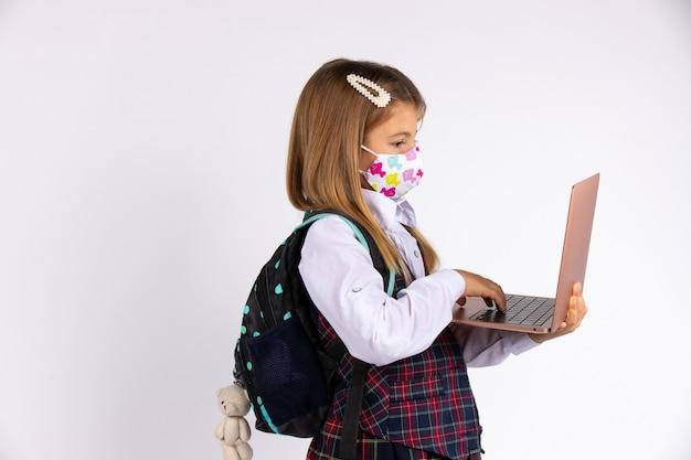 Porträt des grundschülers in uniform mit medizinischer gesichtsmaske, die nach covid-19-quarantäne und -versperrung zurück zur schule geht. rucksack und laptop in händen.