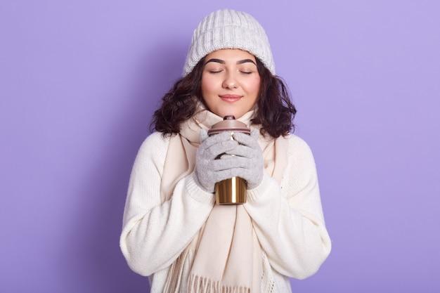 Porträt des gut aussehenden entzückenden jungen mädchens, das steht, ihre augen schließt, ihre hände mit hilfe des thermischen bechers wärmend