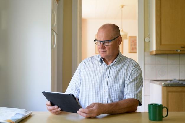 Porträt des gutaussehenden älteren mannes, der zu hause entspannt