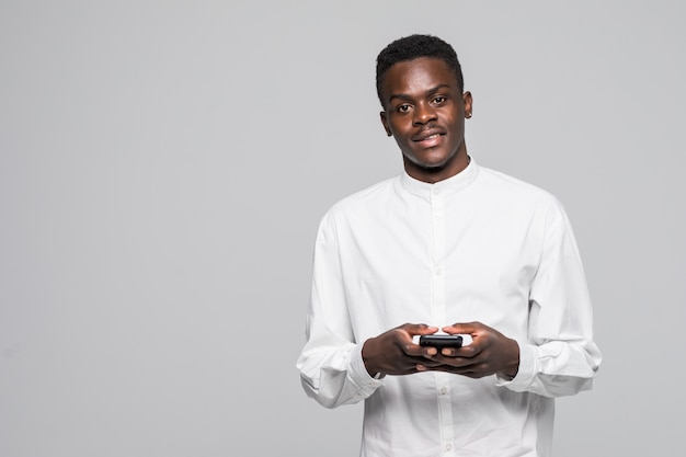 Porträt des gutaussehenden afro-mannes, der nachrichten an seinen geliebten sendet und erhält, lokalisiert auf grauem hintergrund