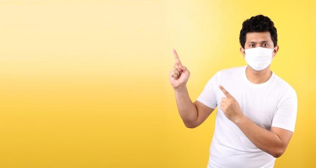 Porträt des gutaussehenden asiatischen mannes, der eine maske trägt, ist krank zeigefinger isoliert