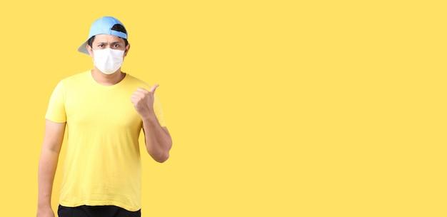 Porträt des gutaussehenden asiatischen mannes, der hüte trägt und eine maske trägt, ist krank zeigerfinger lokalisiert auf gelbem hintergrund im studio mit kopienraum.
