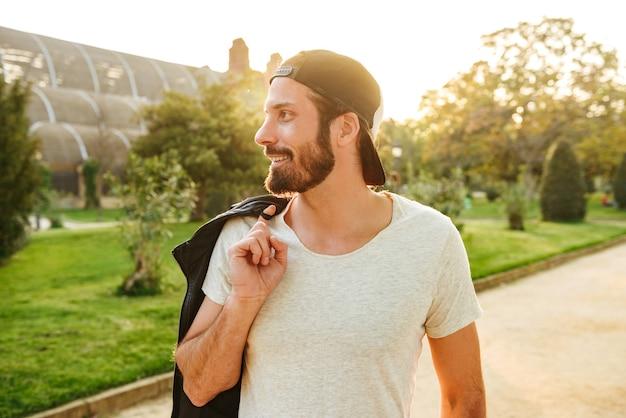Porträt des gutaussehenden bärtigen mannes der 30er jahre, der mütze und weißes t-shirt hält lederjacke auf schulter während des spaziergangs im grünen park hält