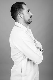 Porträt des gutaussehenden bärtigen persischen arztes auf grau in schwarz und weiß