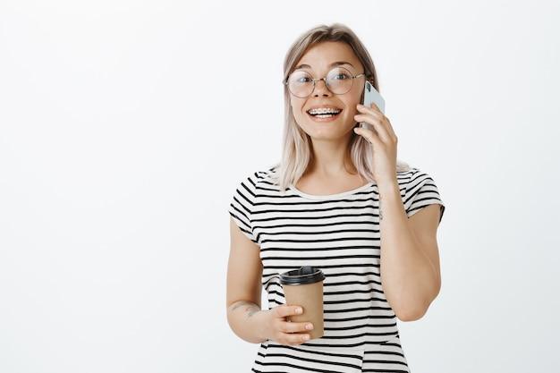 Porträt des gutaussehenden blonden mädchens, das im studio mit ihrem telefon und kaffee aufwirft