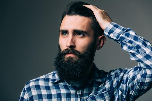 Porträt des gutaussehenden denkenden jungen mannes lokalisiert auf grauer wand