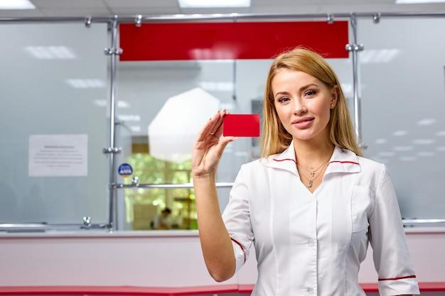 Porträt des gutaussehenden drogerie-arbeiters, der requisiten-karte der apotheke in den händen hält