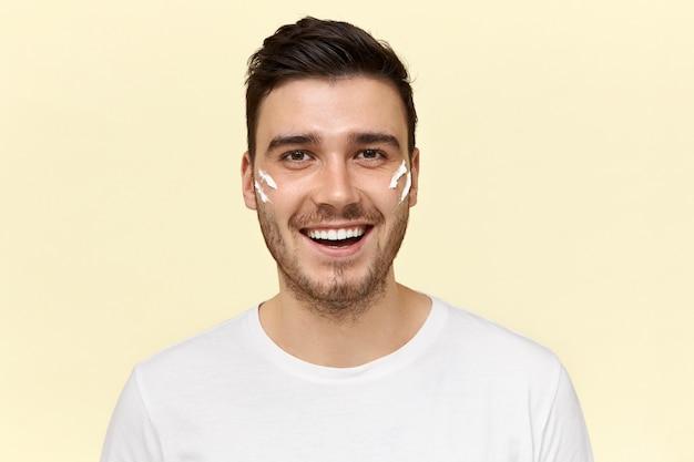 Porträt des gutaussehenden dunkelhäutigen unrasierten mannes, der energetisch glücklichen gesichtsausdruck hat und kamera mit breitem strahlendem lächeln mit streifen der weißen creme auf den wangen betrachtet
