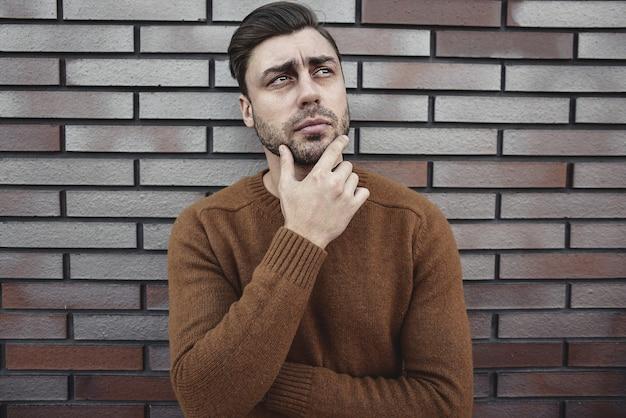 Porträt des gutaussehenden ernsten mannes, der an etwas lokalisiert auf brauner backsteinmauer denkt