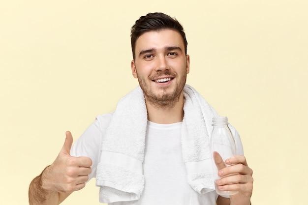 Porträt des gutaussehenden fröhlichen jungen unrasierten mannes mit dem selbstbewussten breiten lächeln, das daumen hoch geste macht, die sich nach dem training im fitnessstudio erfrischt