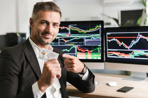 Porträt des gutaussehenden geschäftsmannes der 30er jahre, der anzug hält, der kreditkarte hält, während im büro sitzt und mit digitaler grafik am computer arbeitet