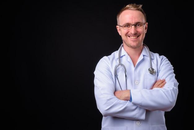 Porträt des gutaussehenden mannarztes mit blondem haar gegen schwarze wand