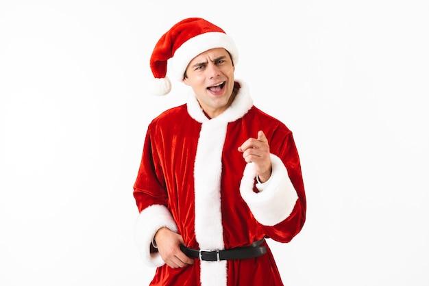 Porträt des gutaussehenden mannes 30s im weihnachtsmannkostüm und im roten hut, der finger auf sie gestikuliert