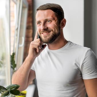 Porträt des gutaussehenden mannes, der am telefon spricht