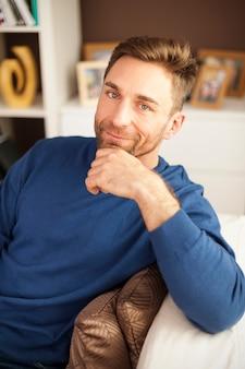 Porträt des gutaussehenden mannes, der auf sofa sitzt
