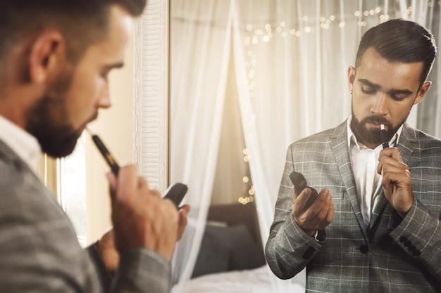 Porträt des gutaussehenden mannes, der ein tabakheizsystem raucht