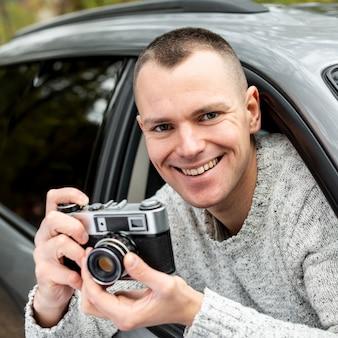 Porträt des gutaussehenden mannes, der eine weinlesekamera verwendet