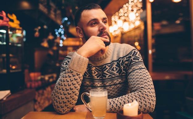 Porträt des gutaussehenden mannes, der etwas trinkt