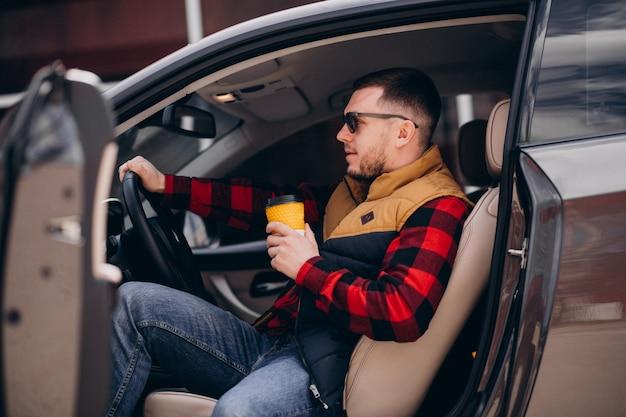 Porträt des gutaussehenden mannes, der im auto sitzt und kaffee trinkt