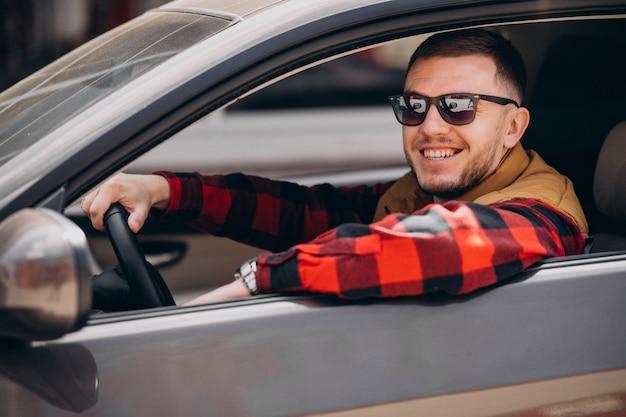 Porträt des gutaussehenden mannes, der im auto sitzt