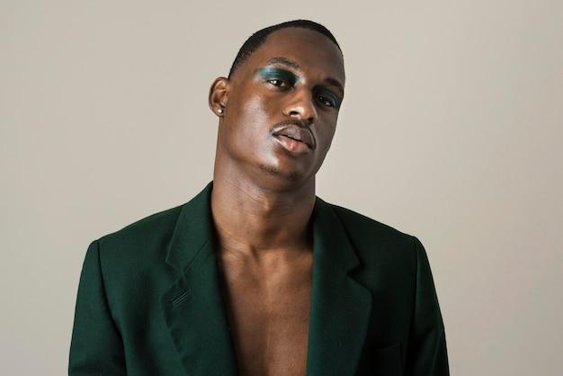 Porträt des gutaussehenden mannes, der im blazer aufwirft und make-up trägt